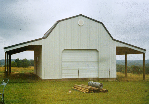 Framed, gambrel roof garage with open-pole sheds